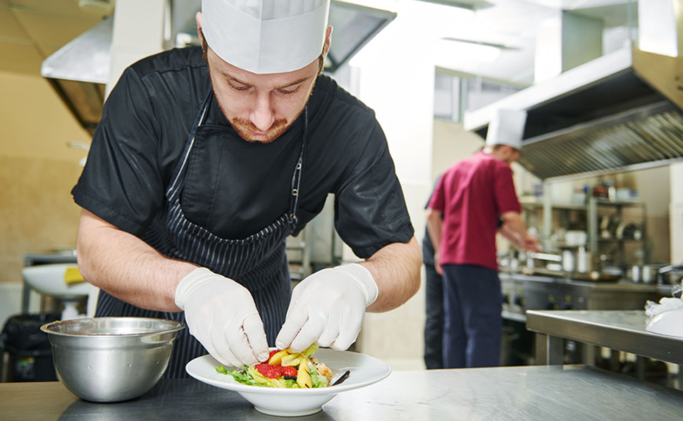 restaurant pos software - a chef preparing food in a restaurant kitchen with team members