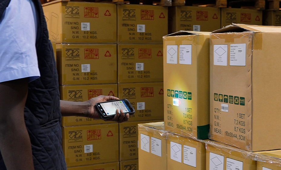 man in a warehouse holding a device for inventory management